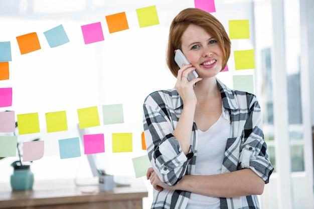 Sonriente mujer hipster, de pie delante de las notas, haciendo una llamada telefónica