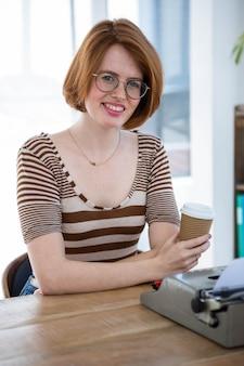 Sonriente mujer hipster sosteniendo una taza de café, frente a su máquina de escribir