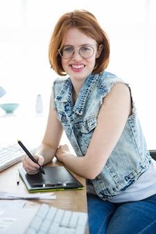 Sonriente mujer hipster, en su escritorio, escribiendo en una tableta de dibujo digital