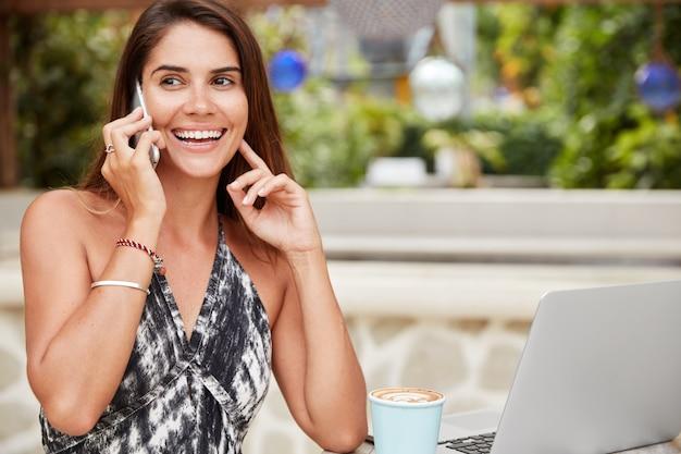 Sonriente mujer independiente relajada que está satisfecha con los negocios en línea, verifica la cuenta bancaria a través de un teléfono inteligente, aprende algo de información en internet en una computadora portátil, bebe café con leche o café caliente