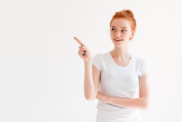 Sonriente mujer de jengibre en camiseta apuntando y mirando a otro lado