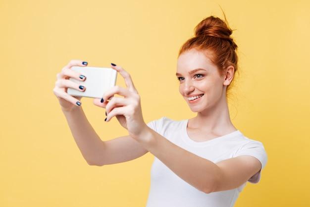 Sonriente mujer de jengibre en camiseta haciendo selfie en su teléfono inteligente