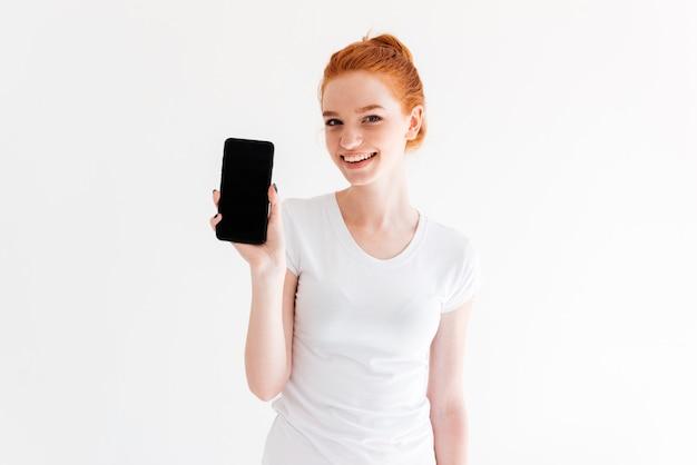Sonriente mujer de jengibre en camiseta mostrando la pantalla del teléfono inteligente en blanco y mirando