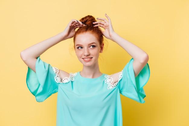 Sonriente mujer de jengibre en vestido corrige su cabello y mirando a otro lado