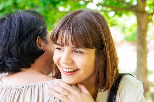 Sonriente, mujer joven, se abrazar, madre, en el estacionamiento