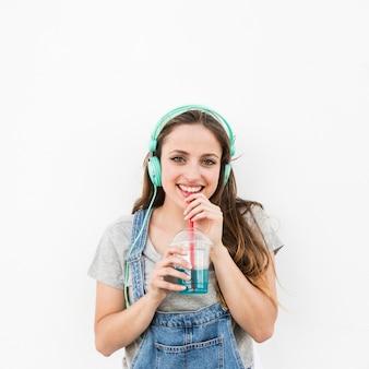 Sonriente mujer joven con auriculares en la cabeza bebiendo jugo
