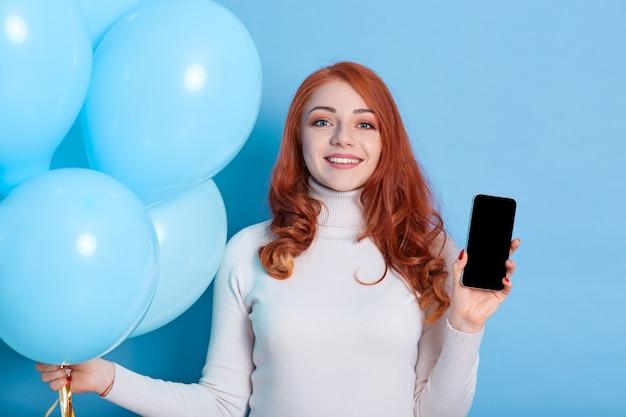 Sonriente a mujer joven y bonita en camisa blanca, sostiene globos azules y teléfono móvil con pantalla vacía en blanco