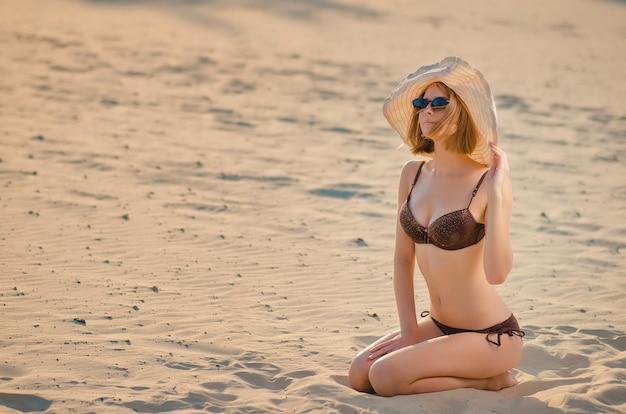Sonriente a mujer joven y bonita con gafas de sol en la playa, está sentada sobre arena dorada