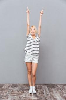 Sonriente a mujer joven y bonita de pie y apuntando hacia arriba con ambas manos