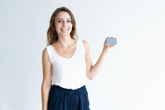 Sonriente mujer joven y bonita que muestra la tarjeta de visita en blanco