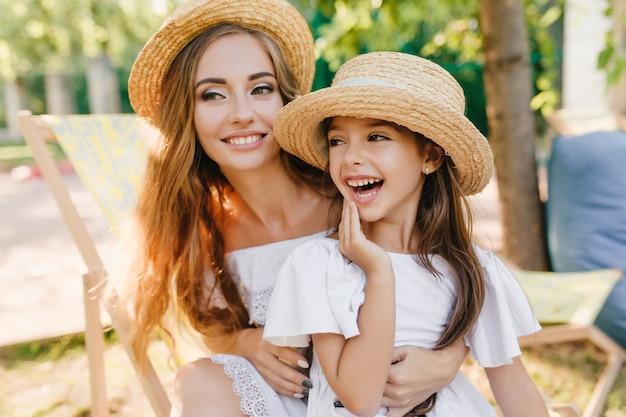 Sonriente mujer joven y bonita y su hija mirando a otro lado mientras pasa tiempo al aire libre en un día soleado. close-up retrato de niña morena divirtiéndose con hermana