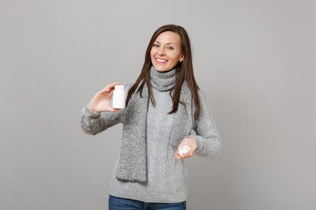 Sonriente a mujer joven en bufanda de suéter gris con tabletas de medicación, píldoras de aspirina en botella aislada sobre fondo gris en estudio. estilo de vida saludable, tratamiento de enfermedades enfermas, concepto de estación fría.