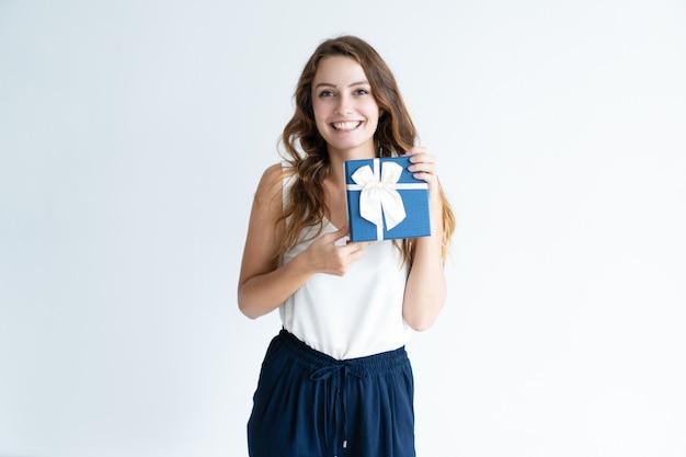 Sonriente mujer joven con caja de regalo con lazo de cinta