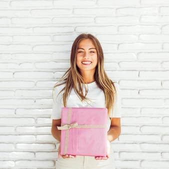Sonriente mujer joven con caja de regalo rosa