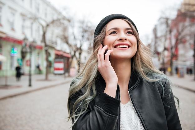 Sonriente mujer joven caminando y hablando por teléfono móvil.