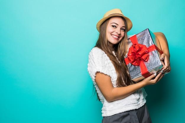 Sonriente a mujer joven en camiseta blanca y sombrero con caja roja presente con cinta de regalo