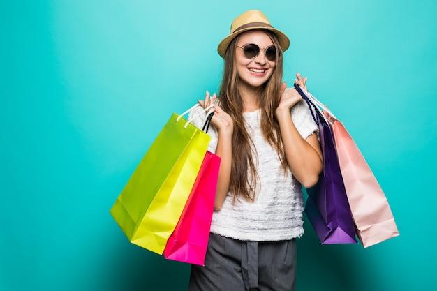 Sonriente a mujer joven en camiseta blanca y sombrero sosteniendo bolsas de la compra.