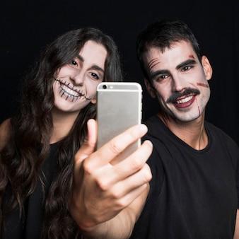 Sonriente mujer joven y chico tomando selfie