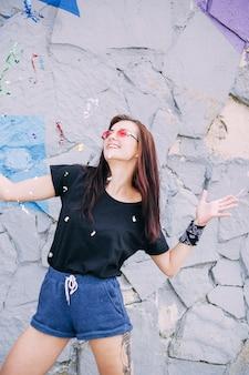 Sonriente mujer joven con gafas de sol posando delante de la pared de piedra pintada