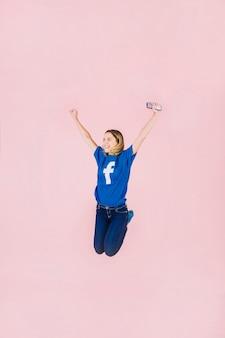 Sonriente mujer joven con smartphone saltando sobre fondo rosa