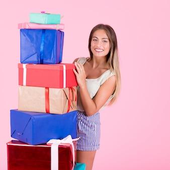 Sonriente mujer joven de pie con pila de regalos sobre fondo rosa