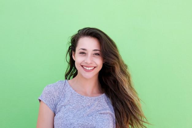 Sonriente mujer joven de pie contra el fondo verde