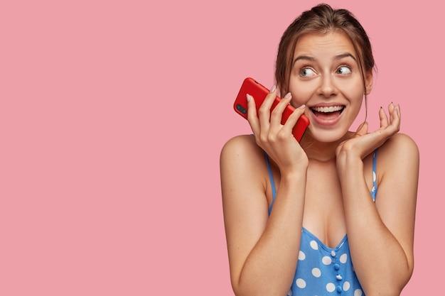 Sonriente mujer joven encantada mantiene moderno teléfono inteligente rojo cerca de la cara