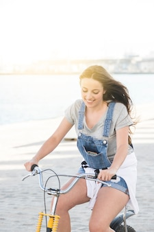 Sonriente, mujer joven, equitación, bicicleta