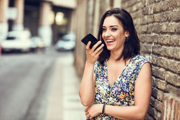 Sonriente mujer joven grabando nota de voz en su teléfono inteligente