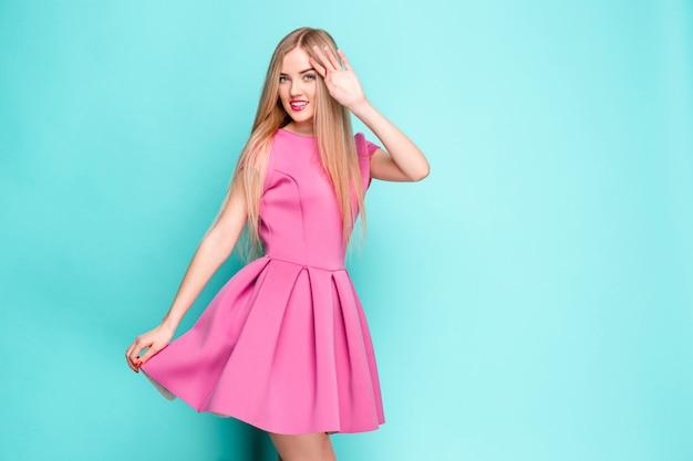 Sonriente a mujer joven hermosa en mini vestido rosa posando en el estudio