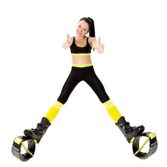 Sonriente mujer joven en kangoo salta zapatos mostrando los dedos hacia arriba