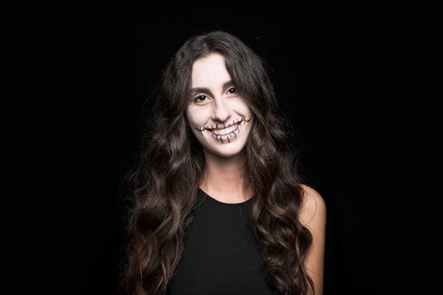 Sonriente mujer joven con maquillaje espeluznante