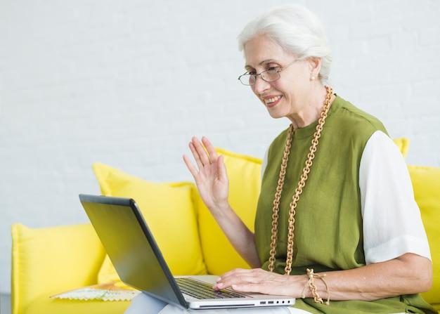 Sonriente mujer joven mirando portátil agitando su mano