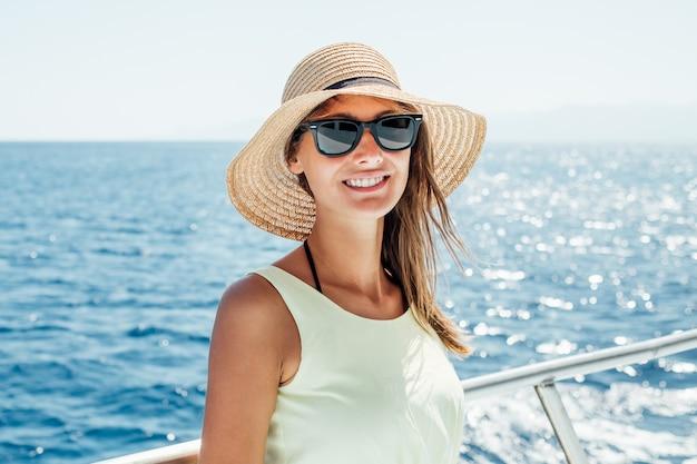 Sonriente mujer joven de pie en un barco durante las vacaciones de verano