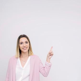 Sonriente mujer joven de pie contra el fondo blanco apuntando hacia arriba