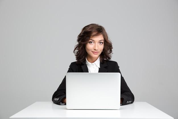 Sonriente a mujer joven rizada hermosa en chaqueta negra sentado y usando la computadora portátil