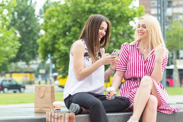 Sonriente mujer joven sentada en el banco mirando el teléfono móvil en el parque