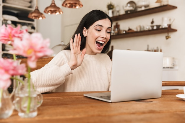 Sonriente a mujer joven sentada en la cocina y usando una computadora portátil, con videollamada