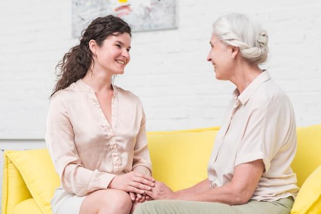 Sonriente mujer joven sentada en el sofá con mujer senior tomados de la mano