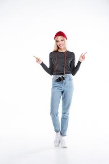 Sonriente mujer joven con sombrero de pie y apuntando dos dedos hacia arriba