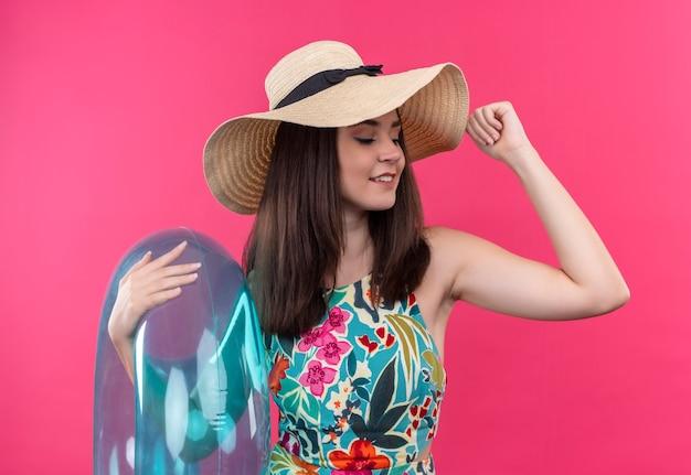 Sonriente a mujer joven con sombrero sosteniendo el anillo de natación y levantando su mano sobre la pared rosa aislada