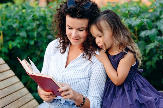 Sonriente mujer joven y su hija leyendo un libro sentado en un banco del parque
