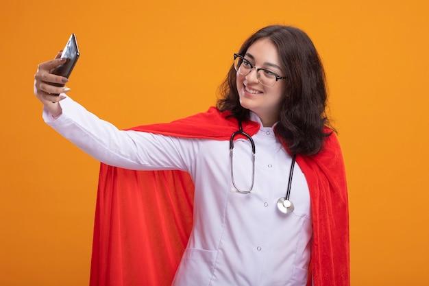 Sonriente a mujer joven superhéroe en capa roja con uniforme médico y estetoscopio con gafas tomando selfie aislado en pared naranja