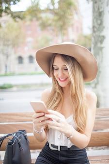 Sonriente, mujer joven, usar, teléfono inteligente, en, banco