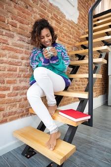 Sonriente mujer latina sosteniendo una taza de café en sus manos. ella está sentada en las escaleras de su casa junto a un libro.