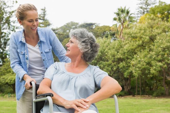 Sonriente mujer madura en silla de ruedas hablando con hija