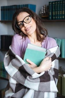 Sonriente mujer madura encantadora cubierta en manta sosteniendo libro