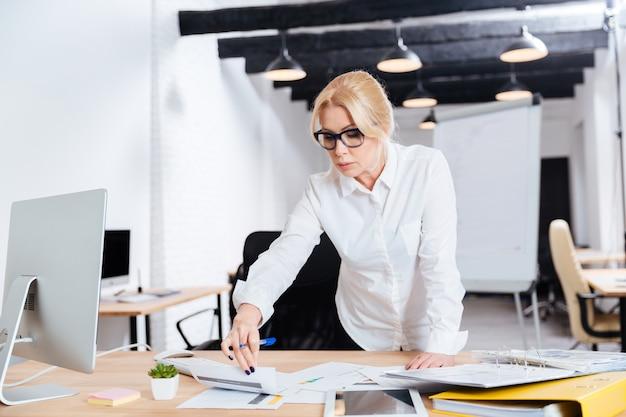 Sonriente mujer madura de negocios de pie y mirando en la computadora diplay