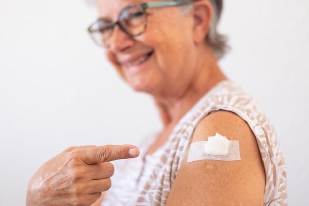 Sonriente mujer mayor de 70 años después de recibir la vacuna contra el coronavirus covid-19.