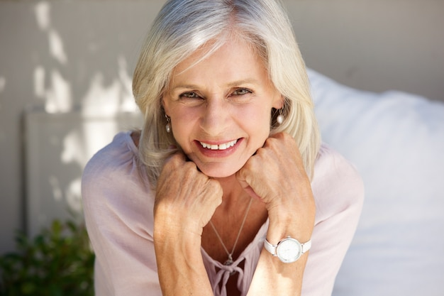 Sonriente mujer mayor con la mano en las manos afuera